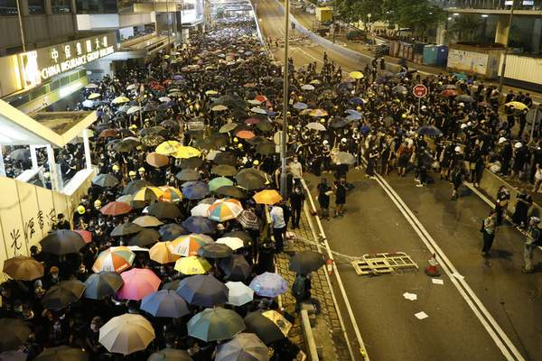 Protesters move along a street in Hong Kong on Sunday, July 21, 2019. (AP Photo/Vincent Yu)
