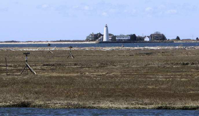 In this April 2, 2019 photo, multimillion-dollar homes and a lighthouse sit on a peninsula in Old Saybrook, Conn. (AP Photo/Dave Collins)