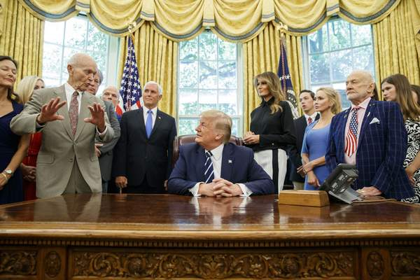 FILE - In this Friday, July 19, 2019, file photo, President Donald Trump, center, listens to Apollo 11 astronaut Michael Collins, left, accompanied by Buzz Aldrin, Vice President Mike Pence and first lady Melania Trump, during a photo opportunity commemorating the 50th anniversary of the Apollo 11 moon landing, in the Oval Office of the White House in Washington. (AP Photo/Alex Brandon, File)