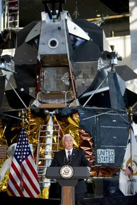 FILE - In this July 16, 2019 file photo, a lunar module, the same type that landed on the moon for Apollo 11, is displayed behind Vice President Mike Pence as he speaks before the unveiling of Neil Armstrong's Apollo 11 spacesuit at the Smithsonian's National Air and Space Museum on the National Mall in Washington. (AP Photo/Andrew Harnik, File)