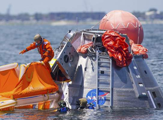 FILE - In this July 13, 2017, file photo, NASA astronaut Mike Fincke jumps into a life raft from an Orion capsule the astronauts are using for a recovery test about four miles off of Galveston Island, Texas in the Gulf of Mexico, the first time since the Apollo program that NASA has practiced such egress techniques from a capsule in open water. (Mark Mulligan/Houston Chronicle via AP, File)