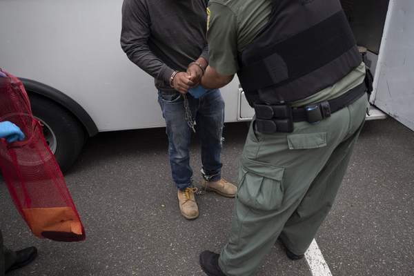 FILE - In this July 8, 2019, file photo, a U.S. Immigration and Customs Enforcement (ICE) officers transfer a man in handcuffs and ankle cuffs onto a van during an operation in Escondido, Calif. (AP Photo/Gregory Bull, File)