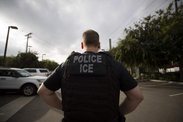 FILE - In this July 8, 2019, file photo, a U.S. Immigration and Customs Enforcement (ICE) officer looks on during an operation in Escondido, Calif. (AP Photo/Gregory Bull, File)
