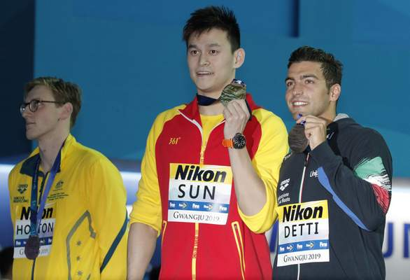 China's Sun Yang, centre, holds up his gold medal with silver medalist Australia's Mack Horton, left, and bronze medalist Italy's Gabriele Detti after the men's 400m freestyle final at the World Swimming Championships in Gwangju, South Korea, Sunday, July 21, 2019. (AP Photo/Lee Jin-man)
