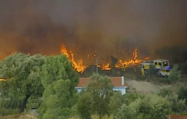 In this grab taken from video on Saturday, July 20, 2019 provided by TVI, members of the emergency services try to extinguish wildfires, in Vila de Rei, Portugal. (TVI via AP)
