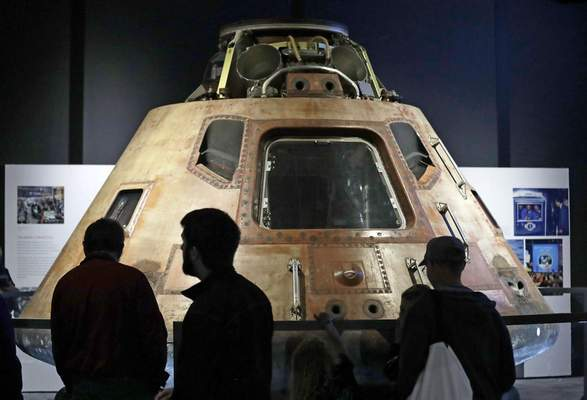 Visitors look at the NASA Apollo 11 command module Columbia, the centerpiece of Destination Moon: The Apollo 11 Mission exhibit at the Museum of Flight, Friday, July 19, 2019, in Seattle. (AP Photo/Elaine Thompson)
