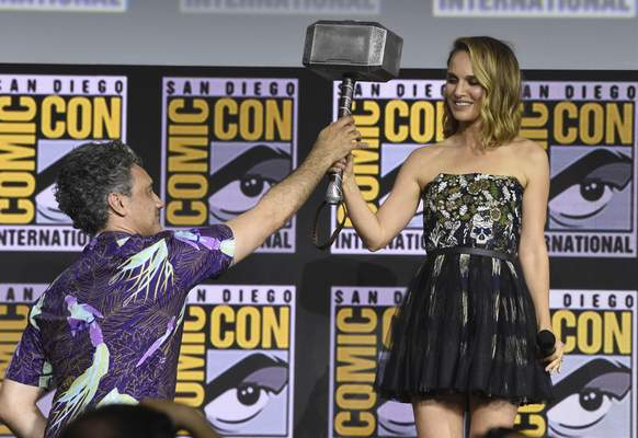 Director Taika Waititi hands the Thor hammer to Natalie Portman during the