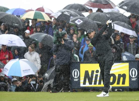 Associated Press Tommy Fleetwood tees off the 9th hole in heavy rain Sunday.