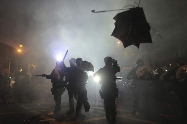 Associated Press A broken umbrella flies past riot police in Hong Kong on Sunday. Hong Kong police launched tear gas at protesters after a massive pro-democracy march continued late into the evening.