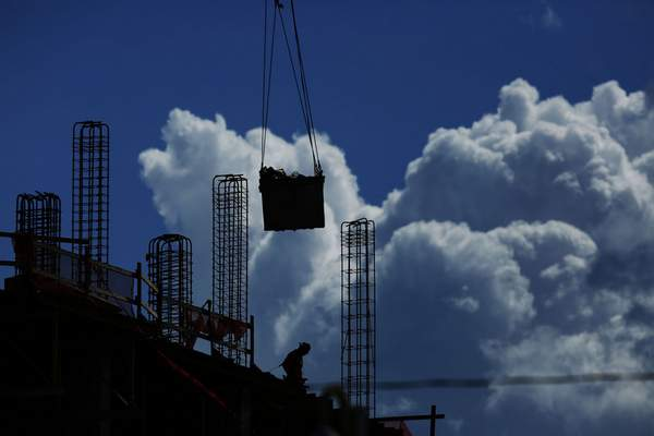 FILE - In this July 2, 2019, file photo a construction worker walks atop a building as a crane lifts a load over head in Miami. On Friday, Aug. 2, the U.S. government issues the July jobs report. (AP Photo/Brynn Anderson, File)
