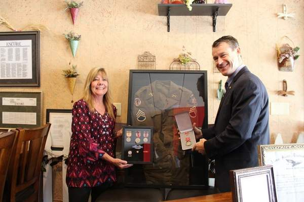 U.S. Sen. Todd Young presents Sandy Dillinger with medals earned by her late father, Robert Egli. Egli died in 1985 and served in the Pacific with an elite Army special forces unit. (Photo courtesy U.S. Sen. Todd Young's office)