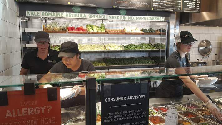 Employees prepare meals at the ordering counter at CoreLife Eatery on Coliseum Boilevard.