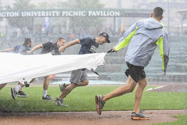 Michelle Davies | The Journal Gazette Members of the Parkview Field grounds crew rush to coverthe playing surface during a storm Tuesday. Play resumed shortly after, but the home TinCaps were sunk by West Michigan 8-0.