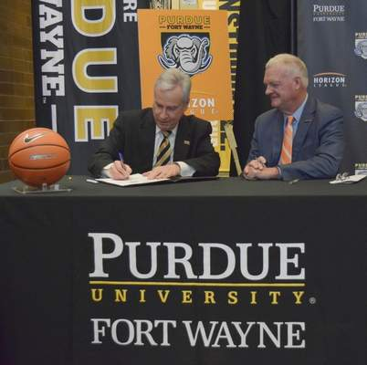 Purdue Fort Wayne Chancellor Ronald L. Elsenbaumer, left, makes the conference move official Tuesday  with Horizon League Commissioner Jon LeCrone.