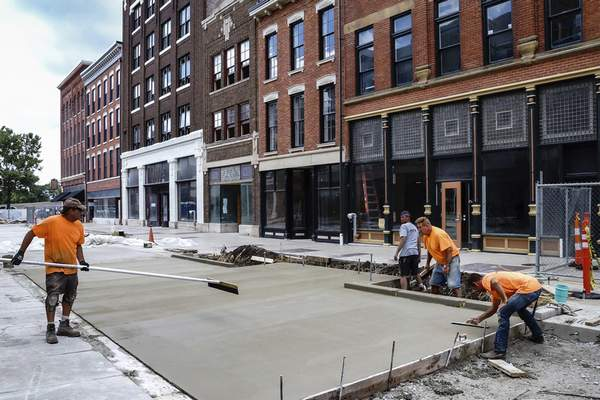 Mike Moore | The Journal Gazette Crews from Sierra Construction smooth out concrete Tuesday while repaving Columbia Street. The Landing revitalization project includes 70 apartments and 56,000 square feet of commercial and retail space.