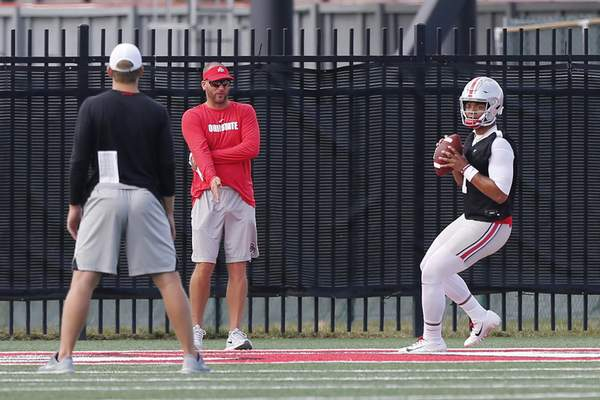 Associated Press Ohio State's Justin Fields drops back to pass during  practice Friday in Columbus, Ohio.