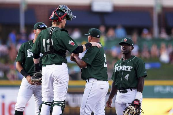 Katie Fyfe | The Journal Gazette  TinCaps players meet in the middle of the field to talk about their next move during the fourth inning against the Dayton Dragons at Parkview Field on Thursday.