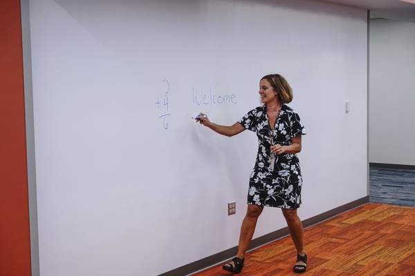 Jenny Fedele, principal of Lafayette Meadows Elementary School, writes on a dry-erase wall in a newly opened wing of Lafayette Meadows Elementary School during a media walkthrough on Thursday. (Mike Moore | The Journal Gazette)
