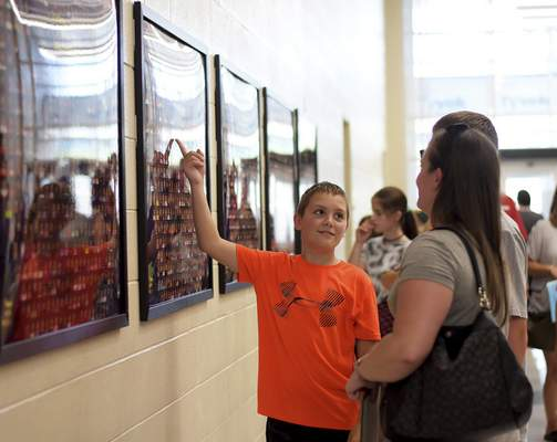 Brayden Schreiber, 10, points out his picture on one of the framed photos of the students, faculty and staff of New Haven Intermediate School during the ribbon-cutting ceremony Thursday. (Katie Fyfe | The Journal Gazette)