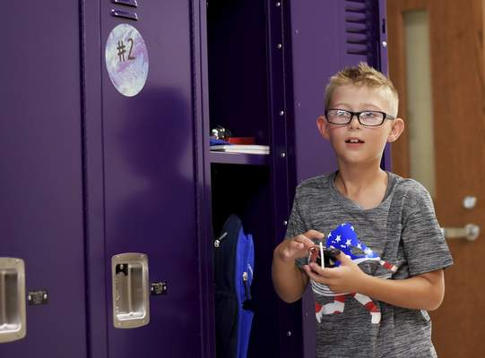 Leighton Beard, 8, puts his supplies into his new locker during the ribbon-cutting ceremony and parents' night at New Haven Intermediate School on Thursday. (Katie Fyfe | The Journal Gazette)