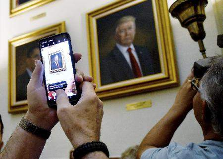 Associated Press: In this Aug. 1, 2019, file photo, people take photos of President Donald Trump's portrait hanging in the Colorado Capitol after an unveiling ceremony in Denver. On Friday, the Associated Press reported on a manipulated video circulating online incorrectly asserting that the painting of President Barack Obama, left, fell off the wall as Trump's was unveiled.