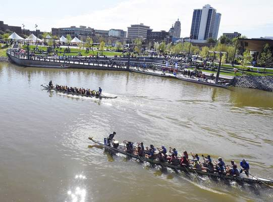 Rachel Von Stroup | The Journal Gazette  Guests watch as the SDI #1and Lincoln Dragon Slayers teams race to the finish during the Dragon Boat Races at Promenade Park on Saturday.