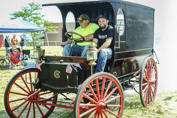 Mike Moore | The Journal Gazette After getting their 1911 International Harvester vehicle started Saturday, Lance Parker, left, and Devan Fryback take it out for a spin.