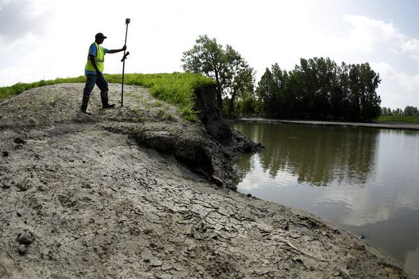 In this Tuesday, Aug. 6, 2019 photo, U.S. Army Corps of Engineers worker Ron Allen uses a GPS tool to survey the extent of damage where a levee failed along the Missouri River near Saline City, Mo. (AP Photo/Charlie Riedel)