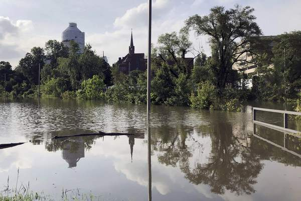 The Missouri Capitol, which is wrapped in plastic while under renovation, is reflected in floodwaters that submerged a parking lot for state employees in Jefferson City, Mo., on Wednesday, May 29, 2019. (AP Photo/David A. Lieb)