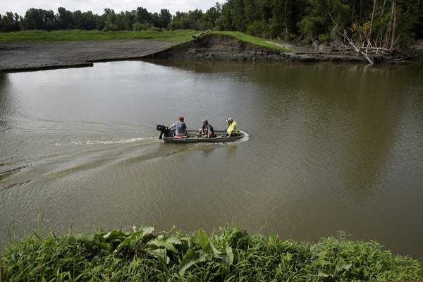 In this Tuesday, Aug. 6, 2019 photo, a survey crew for the U.S. Army Corps of Engineers crosses 20-foot-deep flood waters that remain after a levee failed along the Missouri River near Saline City, Mo. (AP Photo/Charlie Riedel)