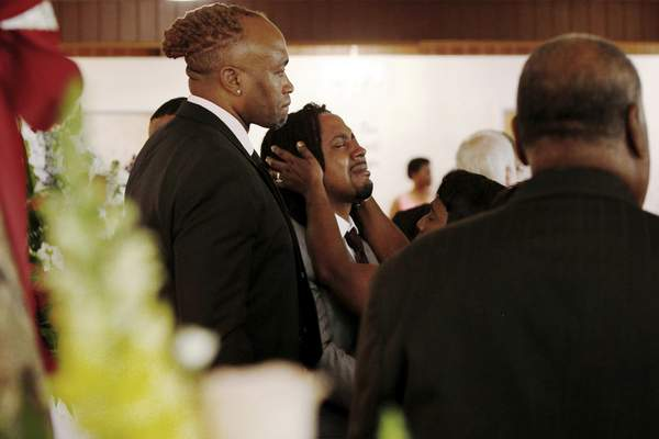 A relative attempts to console Dion Green, center, before the funeral for his father, Derrick Fudge, on Saturday, Aug. 10, 2019, at a church in Springfield, Ohio. Fudge, 57, was the oldest of nine who were killed when a gunman opened fire outside a bar early Sunday in Dayton, Ohio. (AP Photo/Angie Wang)