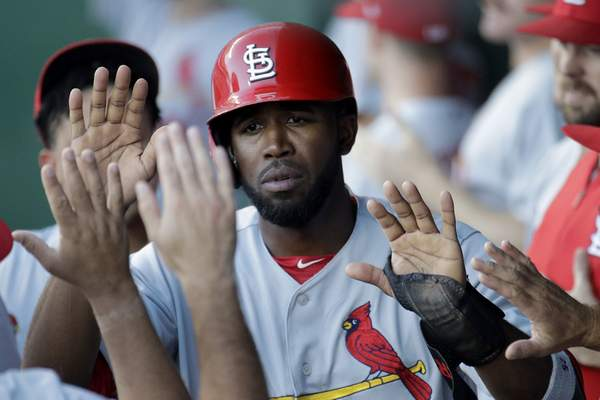 St. Louis Cardinals' Dexter Fowler celebrates in the dugout after scoring on a sacrifice fly hit by Paul Goldschmidt during the first inning of a baseball game against the Kansas City Royals Tuesday, Aug. 13, 2019, in Kansas City, Mo. (AP Photo/Charlie Riedel)
