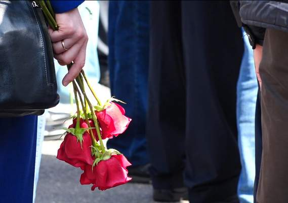 In this grab taken from a footage provided by the Russian State Atomic Energy Corporation ROSATOM press service, a woman holds roses as she and other people gather for the funerals of five Russian nuclear engineers killed by a rocket explosion in Sarov, the closed city, located 370 kilometers (230 miles) east of Moscow, which has served as a base for Russia's nuclear weapons program since the late 1940s, Russia, Monday, Aug. 12, 2019. (Russian State Atomic Energy Corporation ROSATOM via AP)