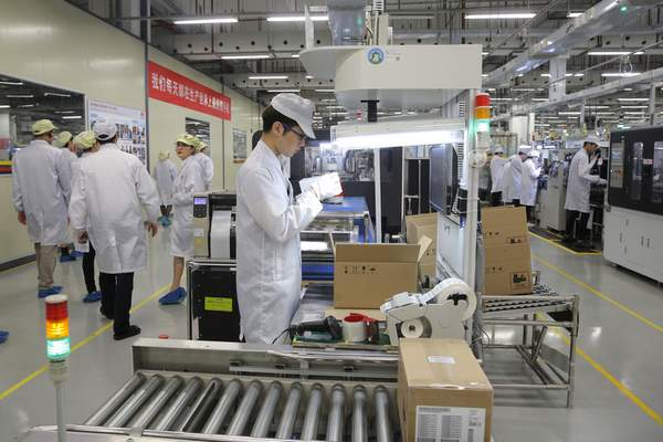 FILE - In this March 6, 2019, file photo a staff member works on a mobile phone production line during a media tour in Huawei factory in Dongguan, China's Guangdong province. (AP Photo/Kin Cheung, File)