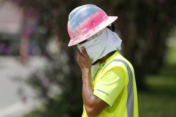 Associated Press Construction worker Dineose Vargas wipes his face Tuesday at a construction site on the Duncan Canal in Kenner, La.