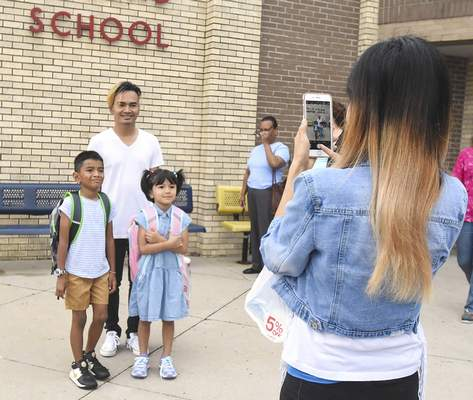 Michelle Davies | The Journal Gazette Khin Thawlaweemhan takes a photo of her husband, Ramonnya Thawlaweemhan , and their two children, James Rainvin, 7,  and Abeber Ramonnya, 5,  as they prepare for their first day of school Tuesday at Holland Elementary. Tuesday was the first day of classes for Fort Wayne Community and Southwest Allen County schools.