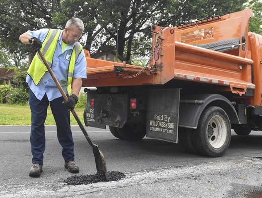 Michelle Davies | The Journal Gazette Duane Gillum with the Fort Wayne Street Department works on filling in potholes Tuesday morning along Curdes Avenue at  Beacon Street.