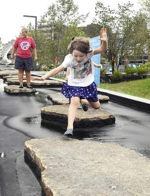 Michelle Davies | The Journal Gazette Anna Palmer, 6, of Fort Wayne leaps Tuesday morning across the stones in the Doermer Kids' Canal at Promenade Park.