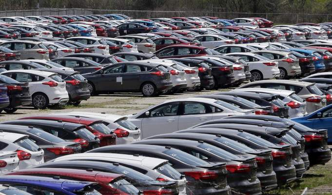 FILE - In this May 1, 2015, file photo Ford Focus vehicles are seen on a storage lot in Ypsilanti, Mich. (AP Photo/Carlos Osorio, File)