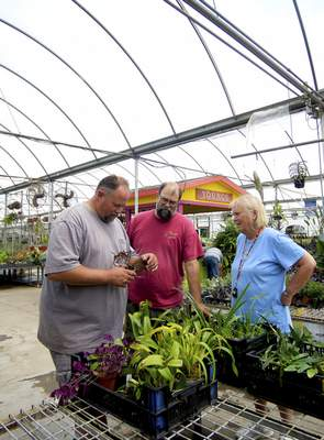 Katie Fyfe | The Journal Gazette Brian, left, and Blake Young check out new plants delivered by Julie Edwards at Young's Greenhouse and Flower Shop. The business is open year-round, but the brothers love working outside in the summer.