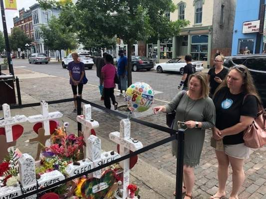 Sabrina Herman, gesturing, visits a makeshift memorial on Wednesday, Aug. 14, 2019, outside Ned Peppers nightclub in the Oregon District entertainment neighborhood where on Aug. 4 a gunman killed nine people, in Dayton Ohio. (AP Photo/Dan Sewell)