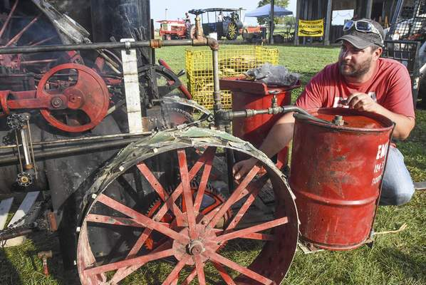 Photos by Michelle Davies   The Journal Gazette ABOVE: Austin Smith loads firewood into a 1919 20H Advanced Rumley steam engine Thursday at the Maumee Valley Steam & Gas Engine Show. The show runs through Sunday at Jefferson Township Park on Webster Road east of New Haven.