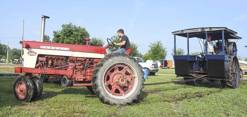 RIGHT: Chris Herman, driving a Farmall 560, pulls Shannon Smith in a 1927 Baker 2175 Heavy-Duty uni flow as part of the engine show.