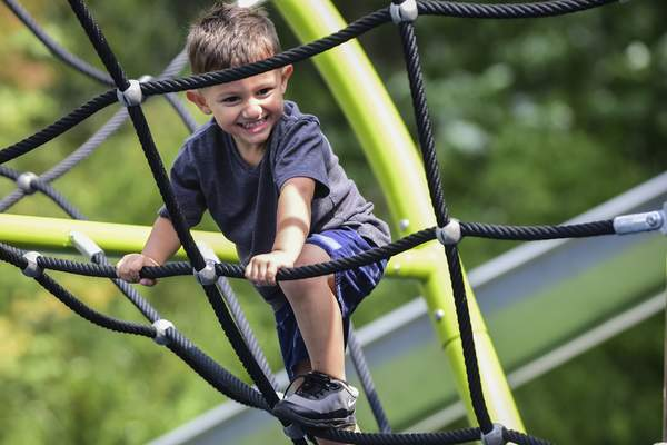 Mike Moore | The Journal Gazette Cayden Rodriguez, 3 climbs the rope ladder at Promenade Park on Thursday.