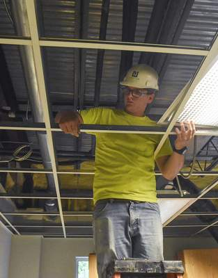 Michelle Davies | The Journal Gazette Payton Knittle with Weigand Construction disassembles a ceiling Thursday at a Lake Avenue office building being renovated to house the new PACE of Northeast Indiana.