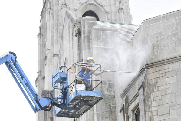 Michelle Davies | The Journal Gazette Doug Rowlett, with Don Rice Construction, uses a pressure washer to clean part of the facade of Plymouth Congregational Church downtown on Tuesday afternoon.