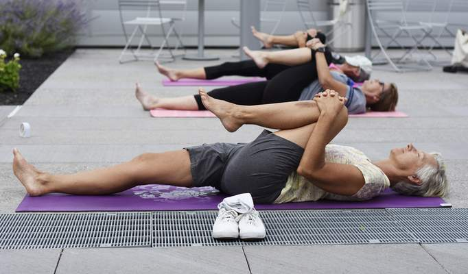 Rachel Von Stroup | The Journal Gazette Beth Monn stretches during a yoga class Thursday atop  the Ash Brokerage building. The class conducted by the YMCA and taught by John Sanner is held at 12:30 p.m. on Tuesdays and Thursdays above the Skyline YMCA. The 45-minute class is for all levels, and participants must be YMCA members.