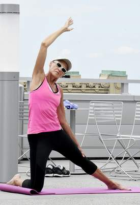 Rachel Von Stroup | The Journal Gazette Linnea Mazock stretches during a yoga class ran through the YMCA taught by John Sanner atop the Ash Brokerage building on Thursday August 22, 2019. The 45 minute all-levels class runs twice a week Tuesday & Thursdays at 12:30pm above the Skyline YMCA and you must be a YMCA member to attend the class.