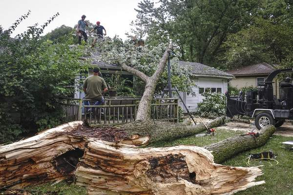 Mike Moore | The Journal Gazette  Charles Douglas, top left, and Paxton Lehman, right, of Charles Douglas Tree Service work to remove a downed tree from a resident's home on Rothman Road after severe weather moved through thearea Sunday morning.