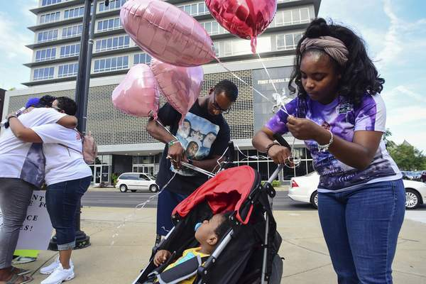 Mike Moore | The Journal Gazette  Friends and family embrace and display their love downtown on Thursday as they hold a vigil in remembrance of Terrance Miles.